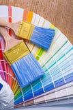 Zwei Malerpinsel auf Farbpalette und hölzernem Brett Stockfotos