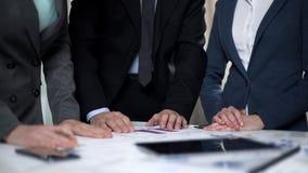 Zwei Managerdamen und männlicher Chef, die Verkaufsdiagramme und Investitionspläne vergleichen stockfoto