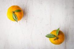 Zwei Mandarinen auf der weißen Draufsicht des Holztischs Lizenzfreie Stockfotos