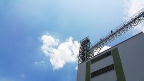 Zwei-mann auf Obertransportmühle und blauem Himmel Stockfoto