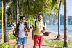 Zwei-mann unter Verwendung der Zelle Smart ruft die tropischen Park-Paare an, die on-line-Feiertags-Seesommer-Ferien plaudern lizenzfreie stockfotos