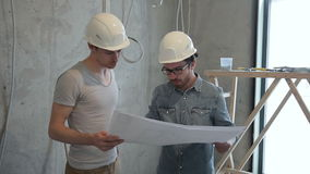 Zwei Mannangestellte, die den Reparaturplan zuhause steht betrachten stock footage