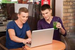 Zwei-mannarbeiten an Computer im Café Lizenzfreie Stockbilder