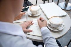 Zwei Mannesunternehmer, der zusammenarbeiten und trinkender Kaffee Stockfotografie
