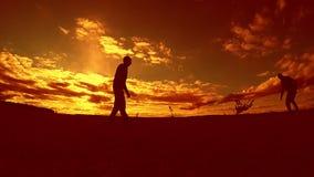 Zwei-mannfußballspieler, der mit Ball während des Sonnenuntergangschattenbild-Zeitlupevideos spielt Männer, die draußen europäisc stock video footage