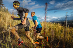 Zwei Mannläufer skyrunners, die ansteigende Spur im Gras auf Hintergrund des blauen Himmels laufen lassen Stockfotografie