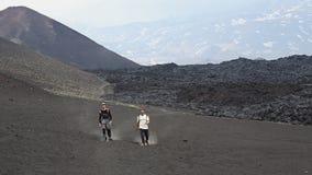 Zwei Manntouristen gehen hinunter den Vulkan, nachdem sie zu übersteigen geklettert sind stock video