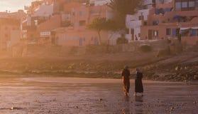 Zwei marokkanisches Frauen walkind in den glühenden Sonnenuntergang Stockbilder