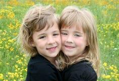 Zwei Mädchen auf dem gelben Blumen-Gebiet Stockfotos
