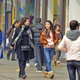 Zwei Mädchen überschreiten durch eine verkehrsreiche Straße Stockfotografie