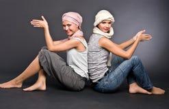 Zwei Mädchen in den Turbanen sitzt auf Fußboden Stockbild