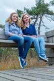 Zwei Mädchen, die auf Holzbank in der Natur sitzen Lizenzfreie Stockfotografie