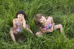 Zwei Mädchen, die im Gras sitzen Lizenzfreies Stockbild