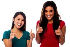 Zwei Mädchen, die oben mit den Daumen oben zujubeln Lizenzfreie Stockfotografie