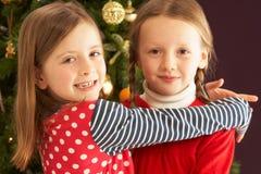 Zwei Mädchen, die vor Weihnachtsbaum umarmen Stockbilder