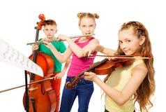 Zwei Mädchen und Junge, die auf Musikinstrumenten spielen Lizenzfreies Stockbild