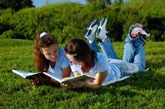 Zwei Mädchenlesebücher draußen in einem Park Stockfotografie