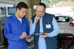 Zwei Mechaniker, die Bestellung im Reifenservice entgegennehmen stockfotografie