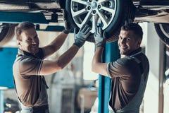 Zwei Mechaniker, die Kamera während Rad-Kontrolle betrachten lizenzfreie stockbilder