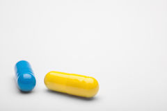 Zwei medizinische Pillen blau und gelb mit Schatten Lizenzfreie Stockbilder