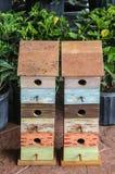 Zwei mehrstöckige selbst gemacht-aussehende Vogelhäuser für Verkauf neben eingemachten Hibiscusanlagen im Frühjahr lizenzfreie stockfotografie