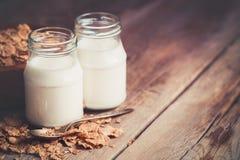 Zwei Milchflaschen und Getreideweizenflocken in der Schüssel zum Frühstück auf Holztisch Kopieren Sie Raum für Text Lizenzfreies Stockbild