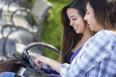 Zwei Mischrasse-Studenten, die Noten-Auflagen-Computer O verwenden stockfoto