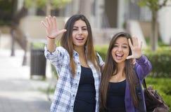 Zwei Mischrasse-Studentinnen, die mit Bacpack wellenartig bewegen Stockfotografie