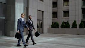 Zwei Mitarbeiter, die Geschäftszentrum lassen, nachdem Partner, Geschäft getroffen worden sind lizenzfreies stockfoto