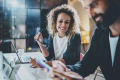 Zwei Mitarbeiter, die Prozessfoto bearbeiten Junge Frau, die zusammen mit Kollegen Nachtam modernen Bürodachboden arbeitet teamwo Lizenzfreie Stockbilder
