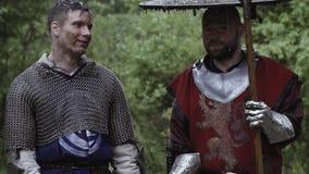 Zwei mittelalterliche Soldaten stehen im Regen und in der Unterhaltung stock footage