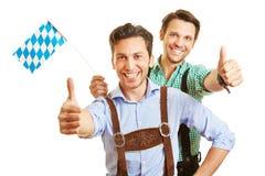 Zwei Männer im Bayern, das Daumen hält Stockfotografie