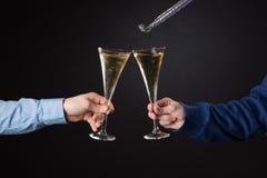 Zwei männliche Hände, die Champagnergläser und Folienausblasen halten Lizenzfreie Stockfotos