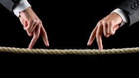 Zwei männliche Hände, die das gehende Zeichen auf einem Seil machen Stockfotografie