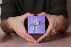 Zwei männliche Hände in Form Herz, das lila Geschenkbox hält Stockbild