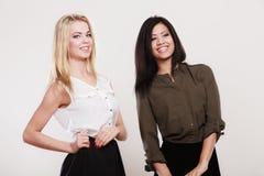 Zwei Modefrauen kaukasisch und afrikanisch lizenzfreies stockbild