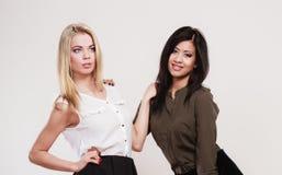 Zwei Modefrauen kaukasisch und afrikanisch lizenzfreie stockbilder