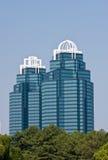 Zwei moderne blaue Büro-Kontrolltürme, die von den Bäumen steigen Stockfotos