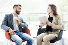 Zwei moderne Geschäftsleute, die in den Stühlen sich entspannen lizenzfreies stockfoto