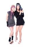 Zwei moderne hübsche stehende und aufwerfende Frauen Stockfotos