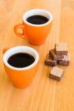 Zwei moderne Kaffeetassen auf einem hölzernen Schreibtisch Lizenzfreies Stockfoto