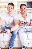 Zwei moderne Kerle, die das Computerspiel hält Prüfer spielen stockfoto
