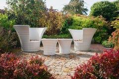 Zwei moderne weiße Gartenstühle und -tabellen auf dem Patio im GA Stockfoto