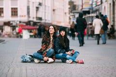 Zwei modisch und scherzende und lächelnde Mädchenskateboardfahrer der modernen Straße Stockbilder