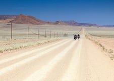 Zwei Motorräder, die schnell auf lange gerade Wüstenstraße fahren Lizenzfreies Stockbild