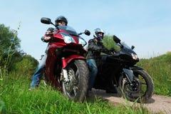 Zwei Motorradfahrer, die auf Landstraße stehen Lizenzfreie Stockfotos