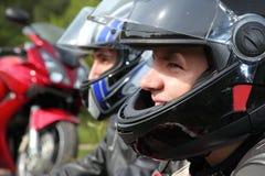 Zwei Motorradfahrer, die nahe Fahrrad sitzen Stockbild