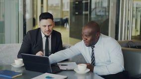 Zwei multi ethnische Geschäftsmänner, die Laptop-Computer betrachten und im glasigen Café lachen Geschäft collaegues, die Spaß ha stock video