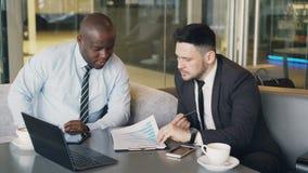 Zwei multiethnische Geschäftskollegen in der formellen Kleidung, die bei Tisch sitzt und Finanzdiagramme beim Betrachten besprich stock video footage