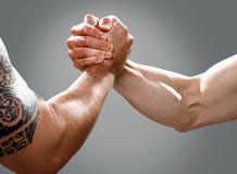 Zwei musculine männliche Hände, die einen Vertrag schließen Lizenzfreie Stockbilder